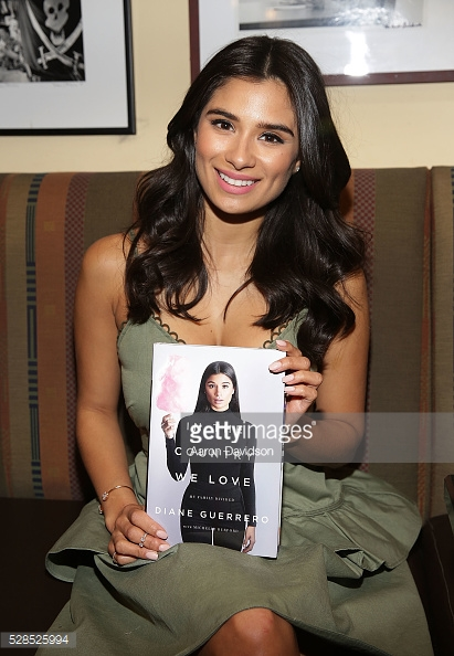 Diane Guerrero is pictured holding her book, In the Country We Love: My Family Divided. The cover of the book pictures Guerrero wearing all black and holding up a cone of pink cotton candy.
