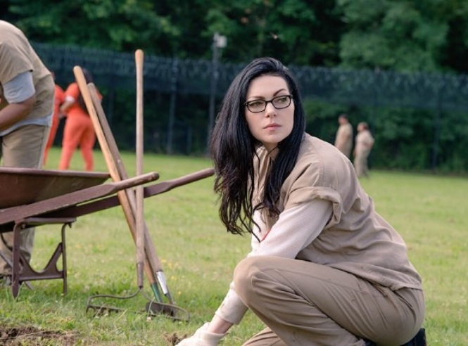 Alex Vause (Laura Prepon) pictured in the prison yard looking suspicious of her surroundings.